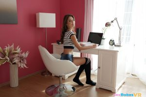 innocent but sexy schoolgirl in knee socks sitting at desk